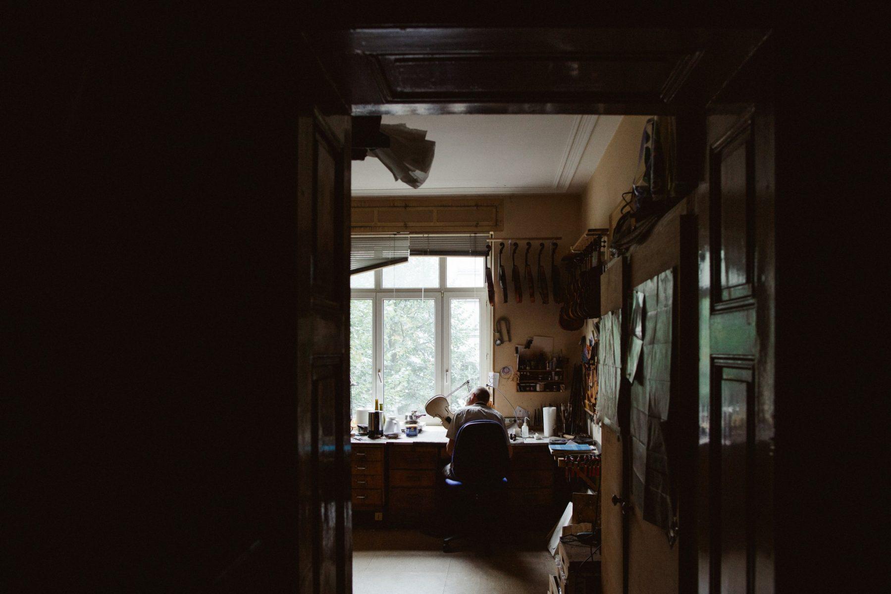 Homme devant la fenêtre réparant violon
